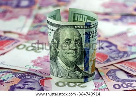 One hundred dollars on Two hundred Ukrainian hryvnia banknotes background - stock photo