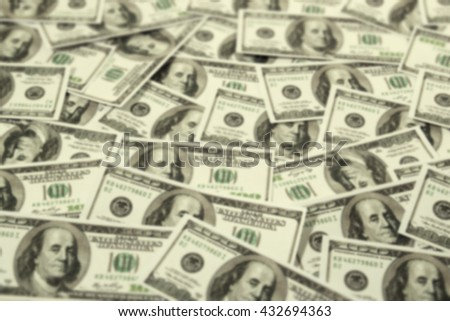One hundred dollars pile as background, abstract blur