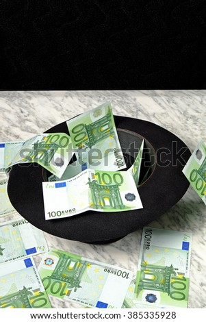 One hundred euro banknotes with a black hat on a marble table on a black background