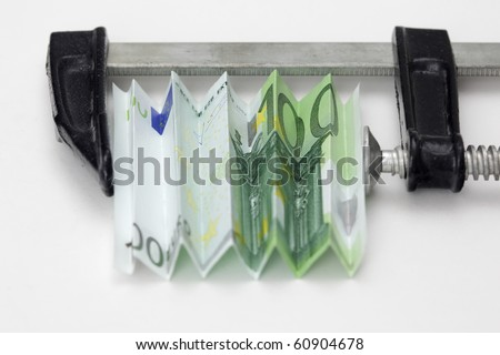 One hundred euro bill squeezed in a clamp on white background - stock photo