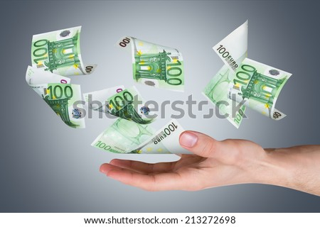 One hundred euro money banknotes flying and falling on young male hand, side view, dark background.