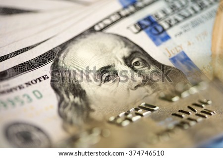 one hundred US dollar bills and credit card