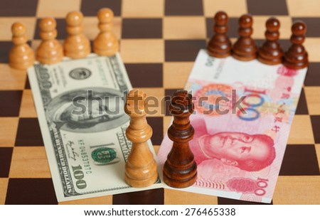 One Hundred US Dollar vs Chinese One Hundred Yuan on a Chess Board - stock photo