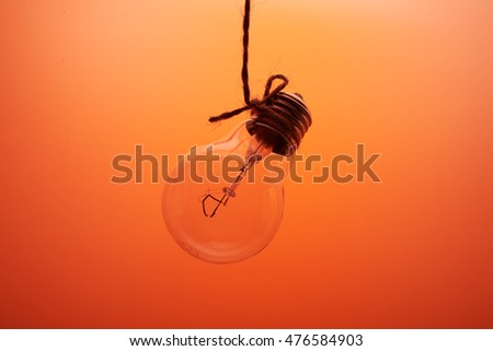 one incandescent lamp on a orange background