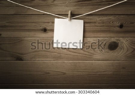 One individual square of note paper, pegged to a string washing line, with wood plank fence in the background.  Low saturation and vignette gives a retro or vintage feel. - stock photo