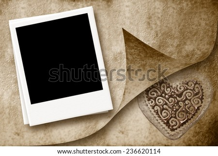 One instant empty photo frame on parchment paper background with a heart - stock photo