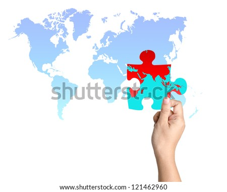 One jigsaw piece of world map held in a hand - stock photo