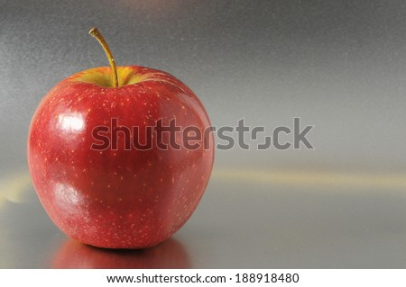 One Juicy Hot Red Apple over a Colored Background