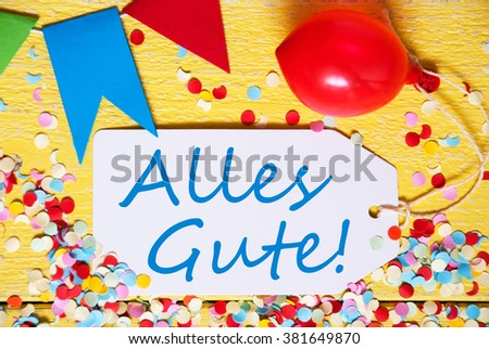 One Label With German Text Alles Gute Means Congratulations. Party Decoration Like Balloon, Confetti And Bunting Flags. Yellow Wooden Background With Vintage, Retro Or Rustic Style. Close Up View - stock photo
