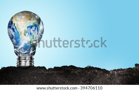 One lamp growth in ground with earth in on blue background - stock photo