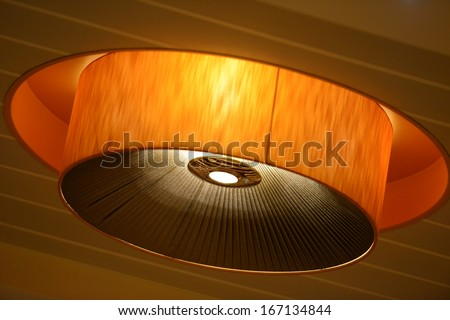 One lamp on the ceiling isolated on wooden texture - stock photo