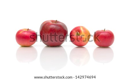 one large and three small apples on a white background with reflection. horizontal photo. - stock photo