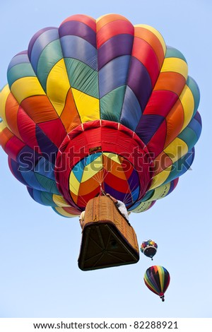 One Large Rainbow Colored Hot Air Balloon With Two More in the Background