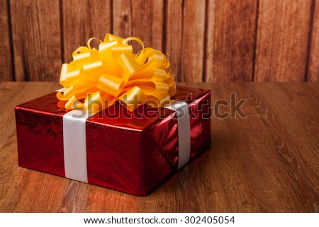 one large red gift box on a wood background