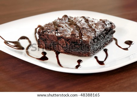 one large square chocolate brownie on a white plate - stock photo