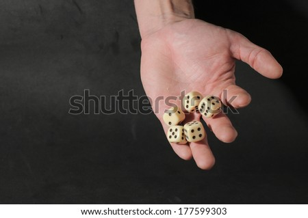 One Left Male Hand Playing Dice on a Black Background
