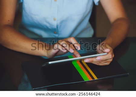 One light-skinned hand belonging to a woman holds a large tablet while the other hand uses a pointer finger to access something on the tablets touch screen display.  The woman in blue shirt. - stock photo