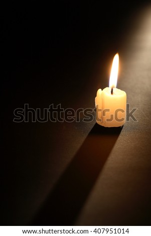 One lighting candle with long shadow on dark background - stock photo