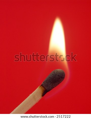One lit wooden matchstick isolated on red background.