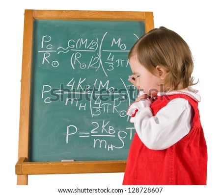 One little girl is writing physics formulas on the blackboard. Horizontal.