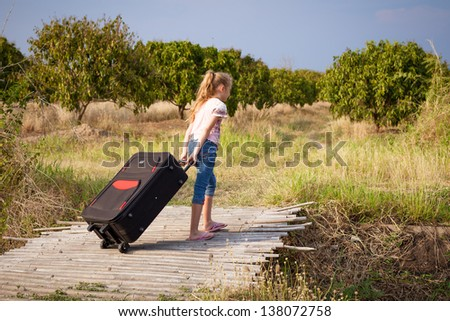 one little girl with suitcase on the road - stock photo