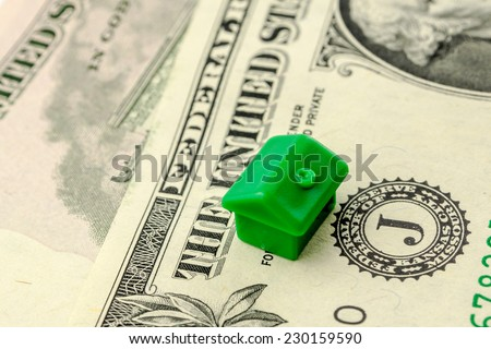 one little green house made of plastic is laying on one dollar banknote, business concept - stock photo