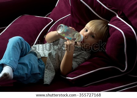 One little pretty blonde baby boy child lying on soft purple sofa in shirt and jeans drinking water from plastic bottle for children looking forward indoor, horizontal picture - stock photo