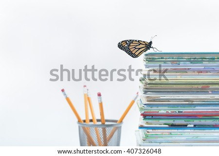One lone monarch butterfly has successfully climbed a large pile of books to the top. The finishing touches of pencils faded into the white background. Horizontal with copy space. - stock photo
