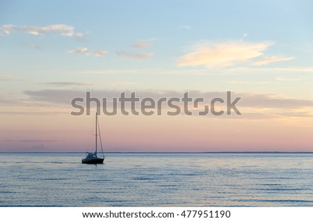 One lone sailboat in calm water by late evening