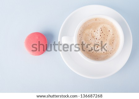 one macaroon and a cup coffee with a heart made of foam on blue background - stock photo