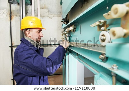 One machinist worker at work adjusting elevator mechanism of lift with spanner - stock photo