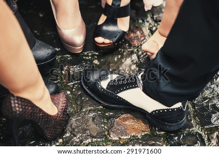 One male black and white shoes among many women