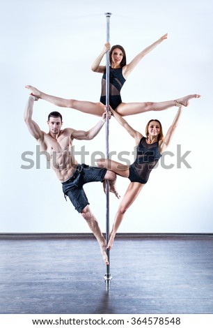 One man and two women pole dance team standing in triangle pose - stock photo