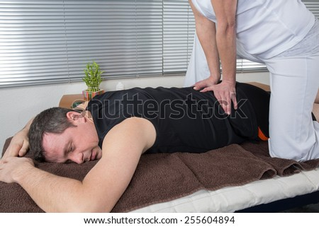 One man and woman performing back  massage - stock photo