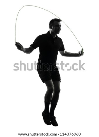 one man exercising jumping rope  in studio silhouette isolated on white background - stock photo