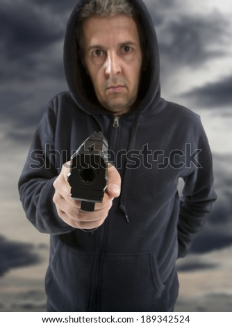 One man gangster is aiming a gun to you - stock photo