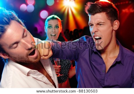 One man hitting another on the face in nightclub, woman watching from background.? - stock photo