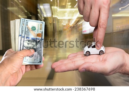 One man holding dollar banknotes, another man holding small car model in auto center - stock photo