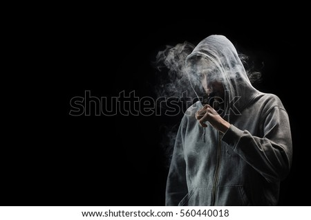 One man in the hood vaping e-cigarette and blowing a cloud.