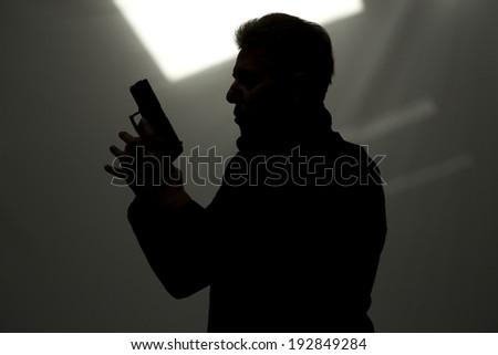 One man killer policeman aiming gun silhouette studio grey background - stock photo