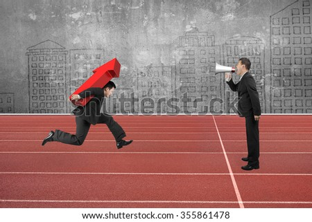One man using speaker to direct another man carrying 3D red arrow up running on track.