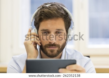 One man watching a movie on tablet pc - stock photo