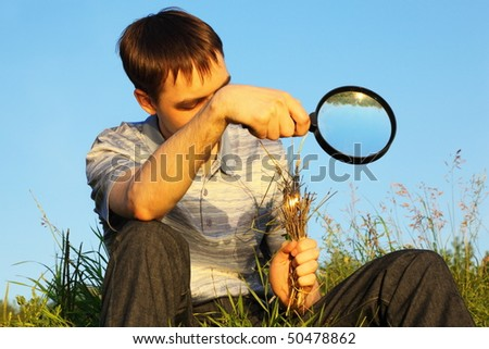 one man wearing shirt and jeans with magnifier is sitting on a meadow and burning grasses - stock photo