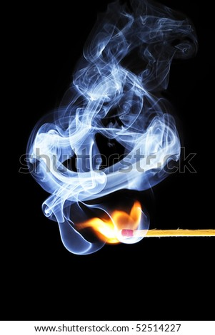 one match is igniting in front of black background with blue smoke - stock photo
