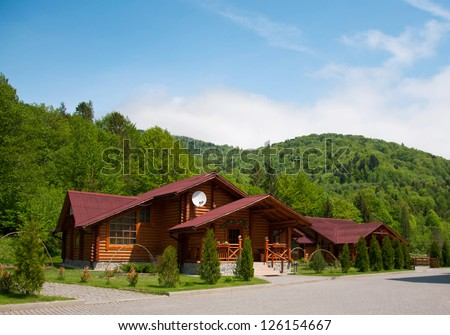 One modern wooden log cabin with all facilities in the mountains with many trees in the forest during spring time. Against blue sky