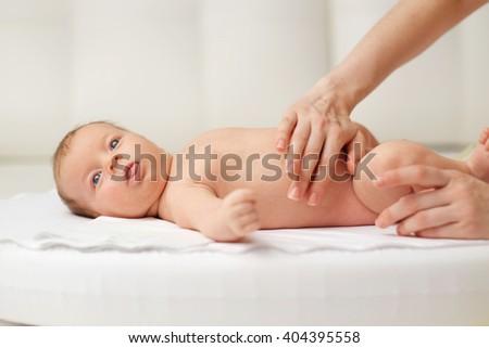 One month old newborn baby massage - stock photo