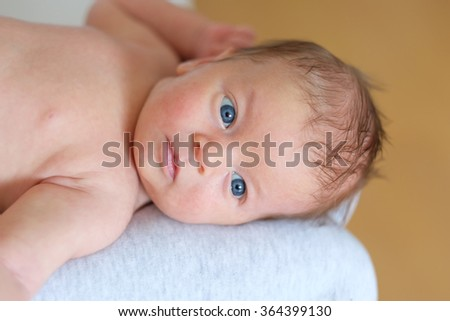 One month old newborn baby with his mother - stock photo