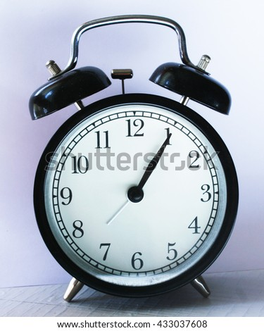 One o'clock, black alarm clock with white clock face