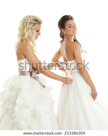 One of brides helps other to lacing corset - stock photo