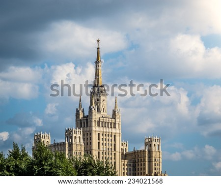 One of Moscow's famous highrises. Blue cloudy sky in background, tree in foreground. Summer in Russia. - stock photo